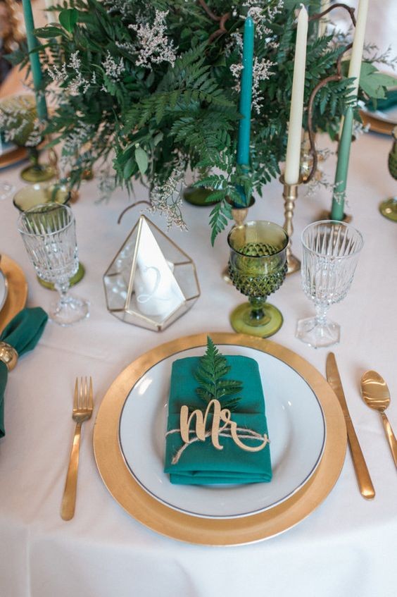 a gold charger and cutlery, green candles and a lush greenery centerpiece, emerald napkins