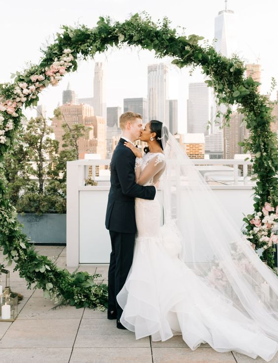 an oversized greenery and blush flower wreath with candles around for a modern rooftop wedding (Styled by Gardenia Organic)