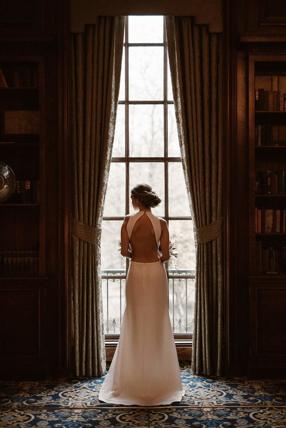 an ultra-modern Sarah Seven wedding gown with a halter neckline and an open back brings wow effect