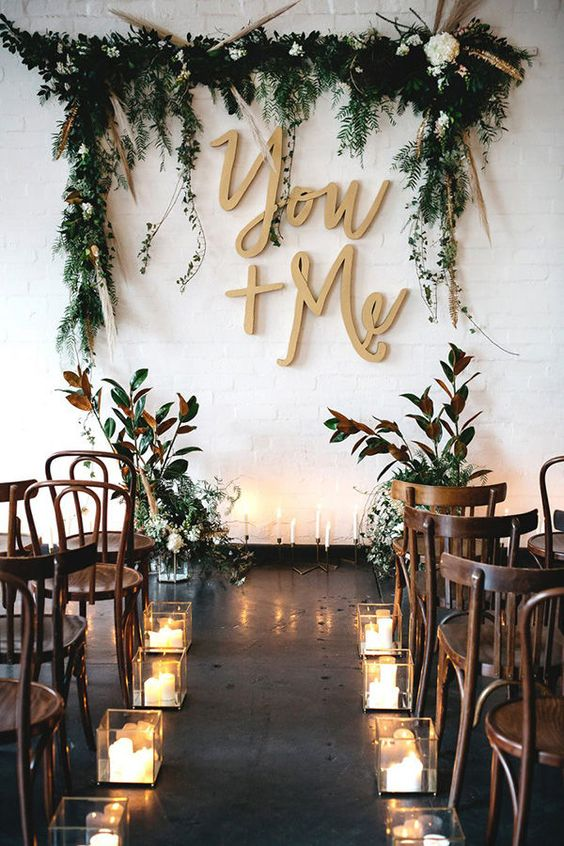 the ceremony space is done with greenery and white blooms, calligraphy letters and candles
