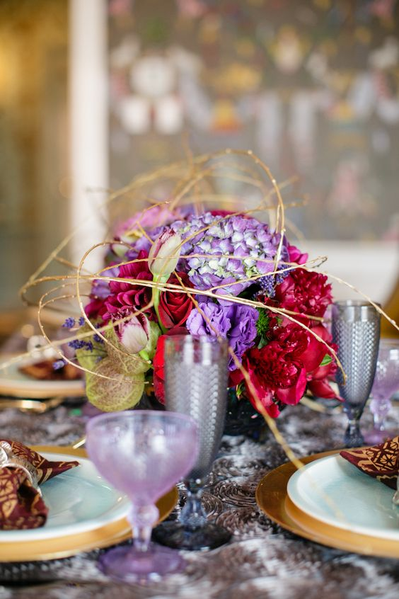 a bold bloom centerpiece in red and ultra violet with gold branches for an eye-catchy dimensional look