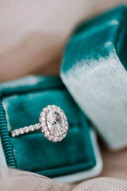 a stunning vintage inspired oval shaped diamond engagement ring with a halo