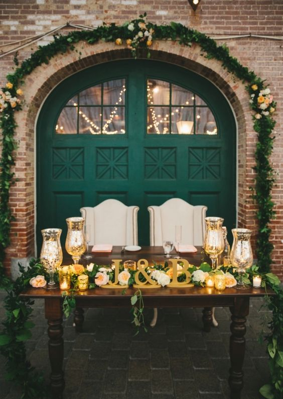 a vintage emerald barn door as a backdrop, gold candleholders, letters and a lush greenery garland