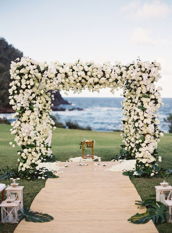 a floral arbor covered with white roses completely and a backdrop of the ocean look wow