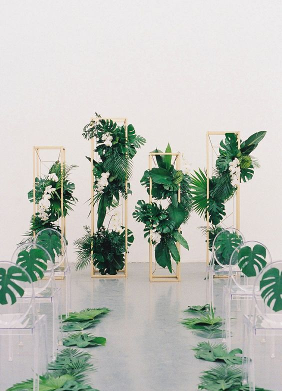 wooden pillars with tropical leaves and blooms and acrylic chairs with palm leaves for a modern tropical wedding
