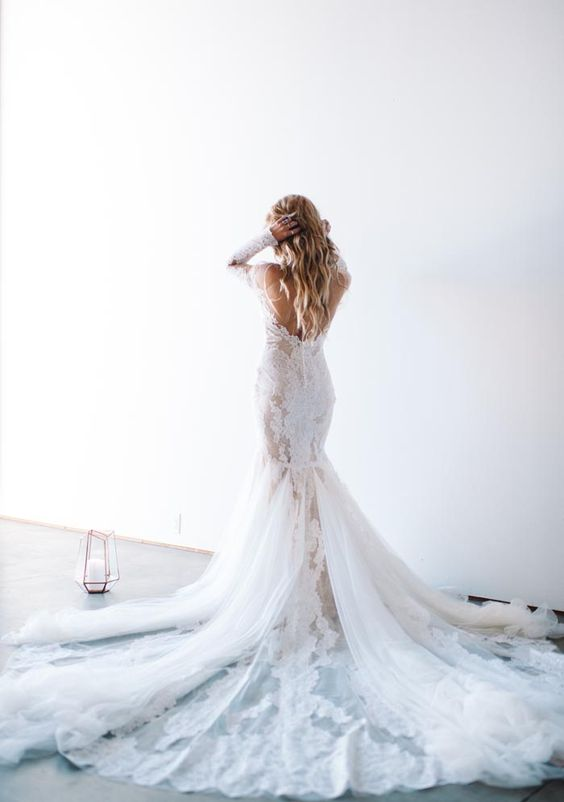 a backess lace applique mermaid wedding dress with long sleeves and a long train looks very chic
