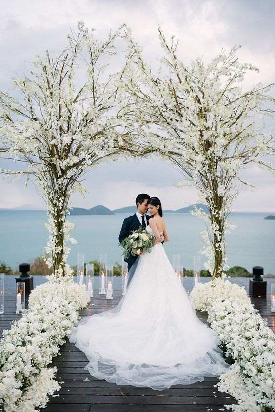 a floral arch composed of two trees and white blooms and white blooms to line up the aisle