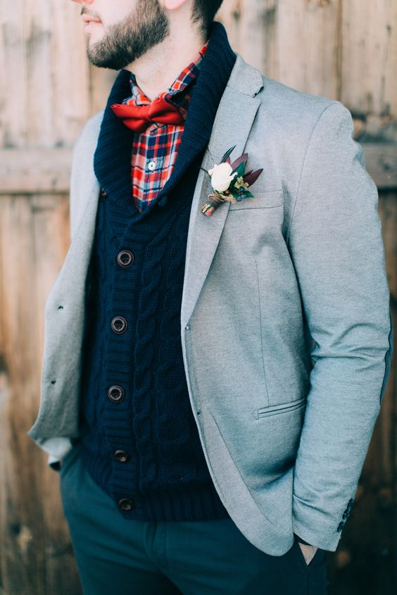 a navy cable knit cardigan, a plaid shirt with a red bow tie, a dove grey blazer for a cozy and wamr outfit