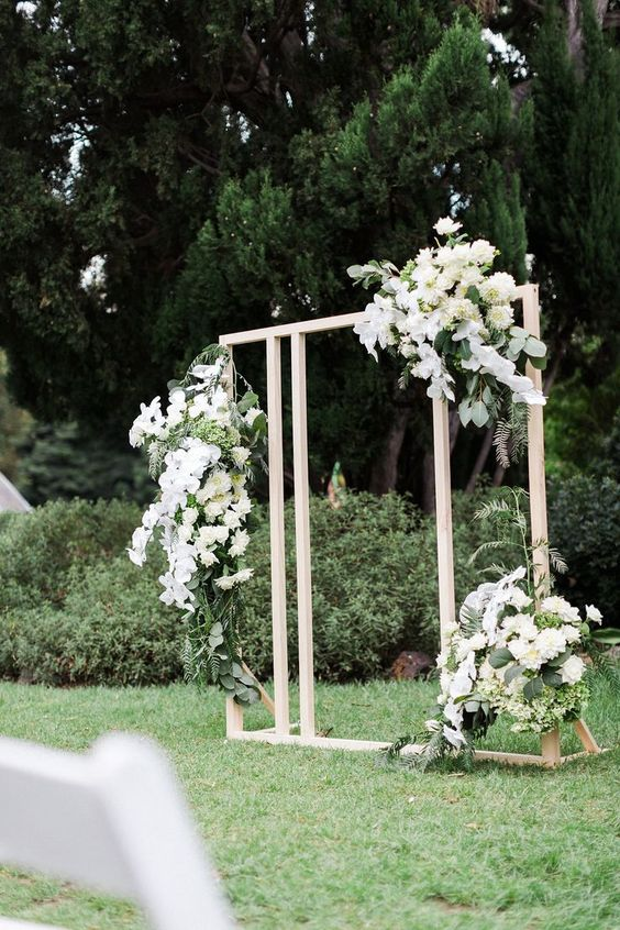 a simple modern white backdrop with lush white florals for a chic and romantic look