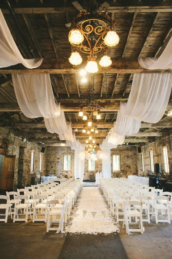 an industrial loft with brick walls, airy white fabric and white petals on the aisle
