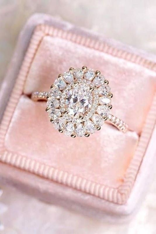 an oval shaped diamond engagement ring with several halos for more bling