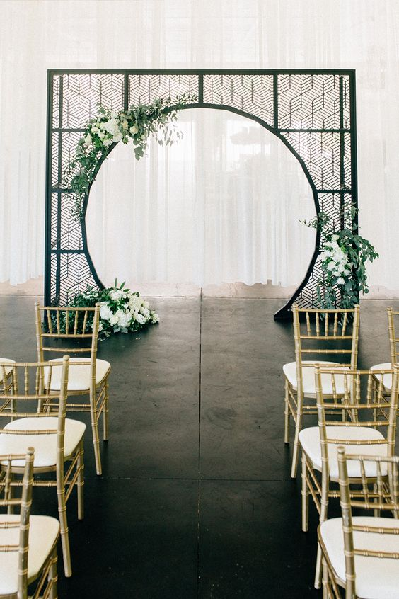 a black forged arch with a round cutout and greenery and white blooms for a modern ceremony