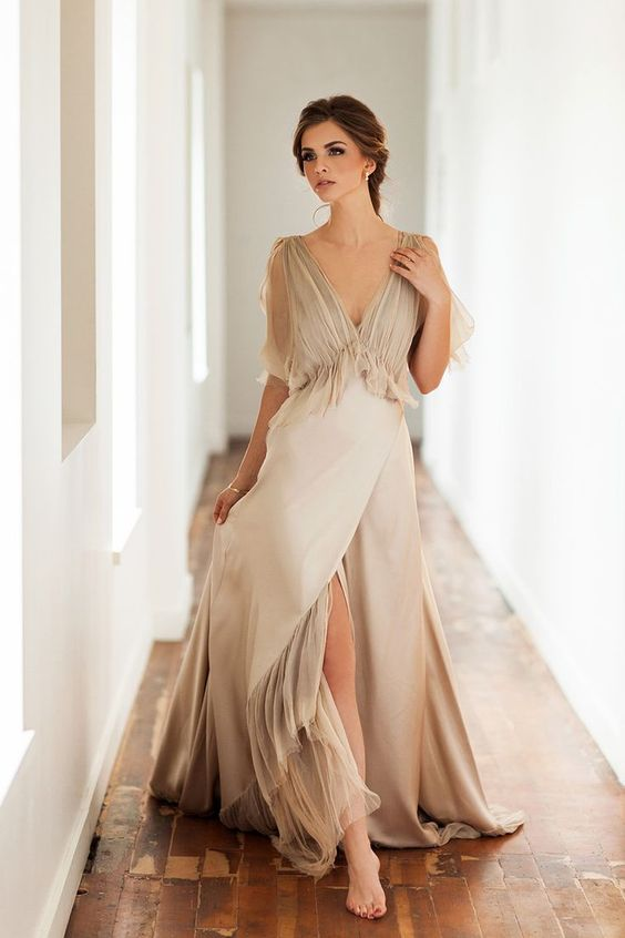 a flowy champagne wedding dress with short sleeves and a draped bodice plus a front slit for a romantic bride