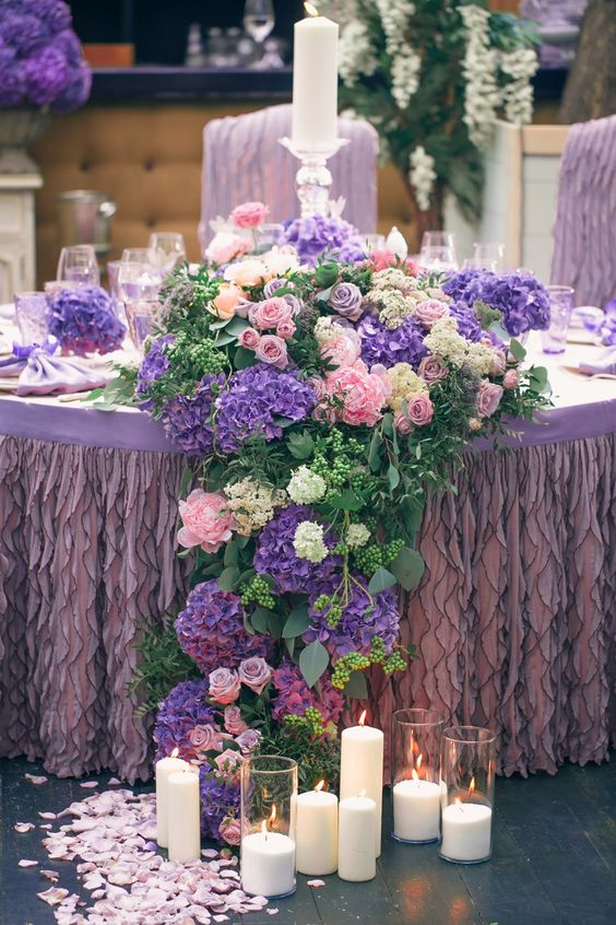a gorgeous lush tablescape with a lilac ruffled tablecloth and pink, white and violet blooms that cascade down the table