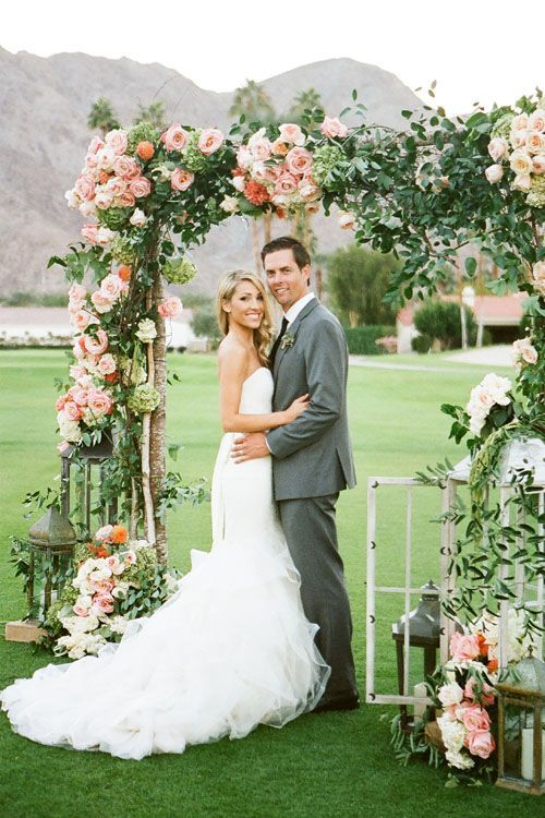 a greenery and peachy roses arch with candle lanterns around for a timeless romantic look