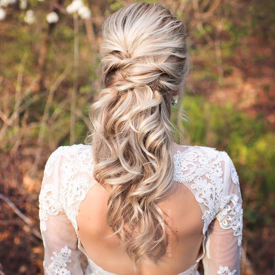 a twisted half up half down hairstyle with waves looks very romantic and beautiful
