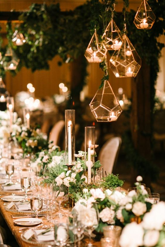 candles in tall vases and geometric candle lanterns hanging above the table for a chic look
