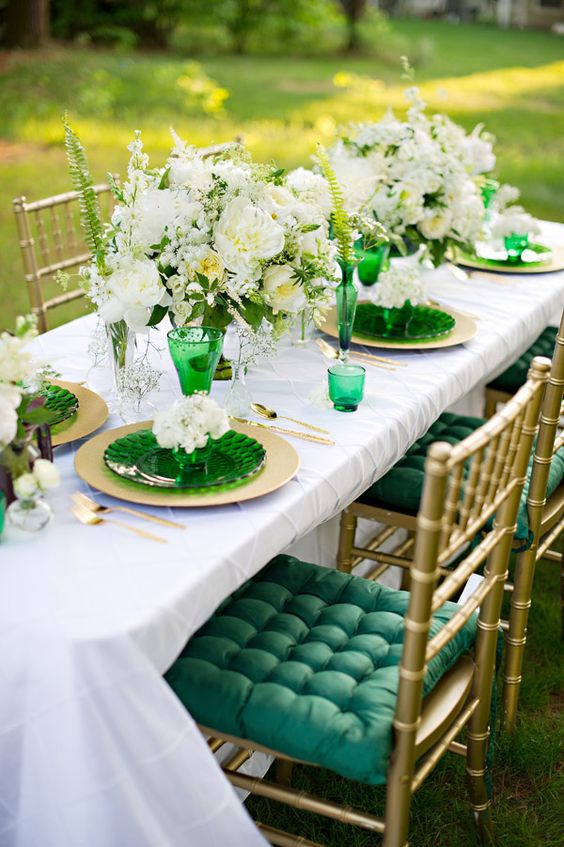 emerald glasses, plates and gold chargers and cutlery, lush white blooms