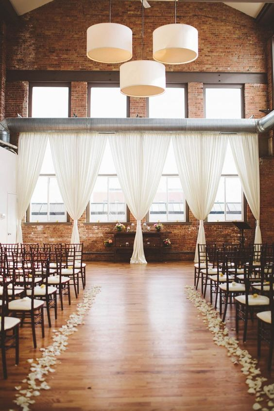 exposed brick walls, double height ceilings and aiy curtains and white petals
