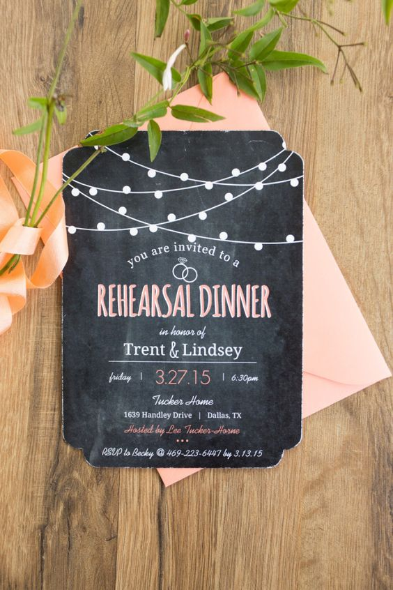 a chalkboard style reahearsal dinner invitation with white and pink letters