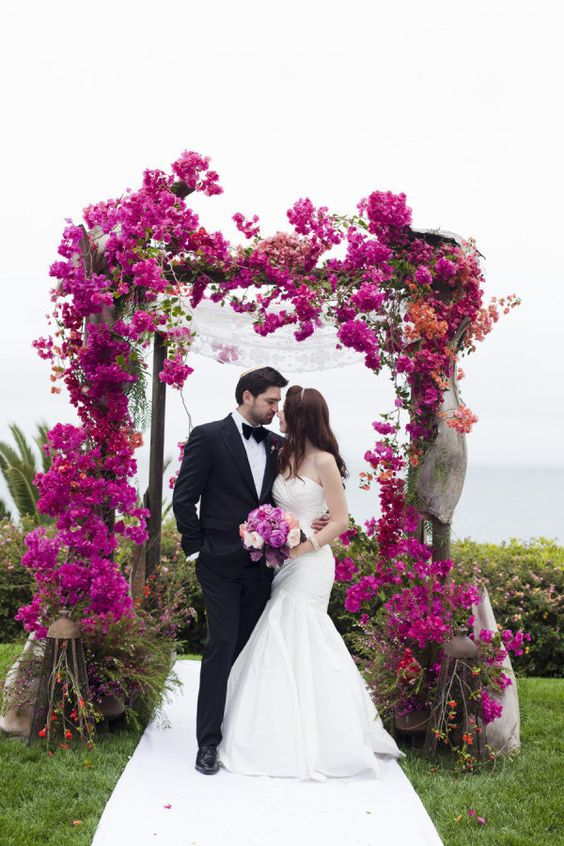 a lush and bold fuchsia bloom wedding arch and a backdrop of the sea behind