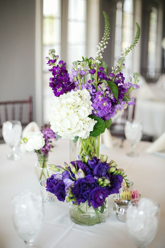 a lush bloom centerpiece with purple, violet and white flowers