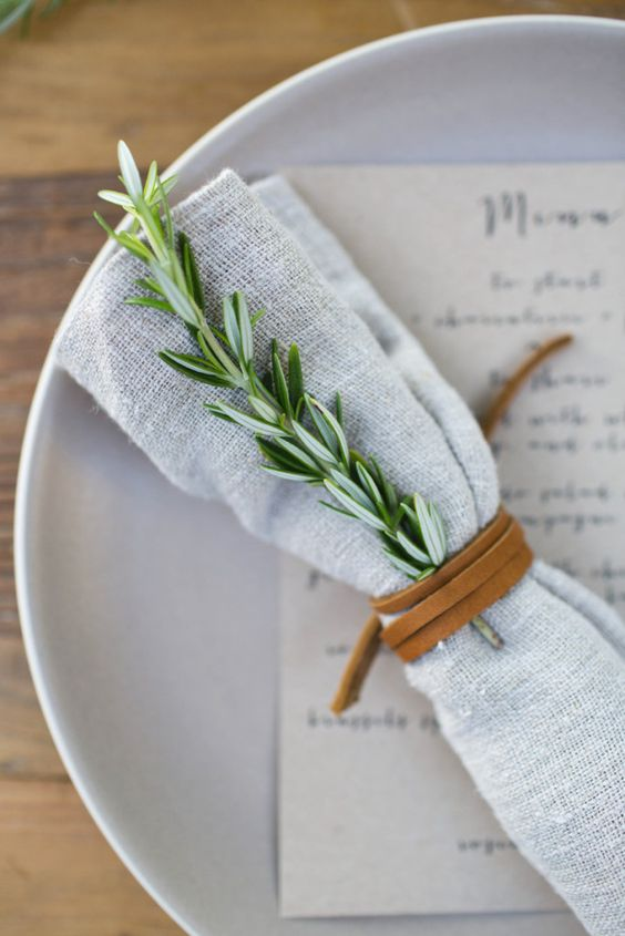 a napkin accessorized with rosemary and a leather cord to make it more eye-catchy