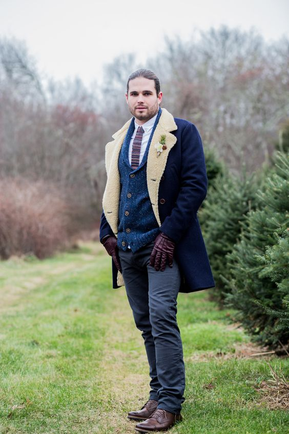 a navy shearling coat with white faux fur, a navy cardigan, a printed tie and a white shirt for a cold weather wedding