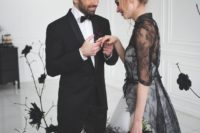 20 cover a white wedding dress with a sheer black lace top with short sleeves and a long train