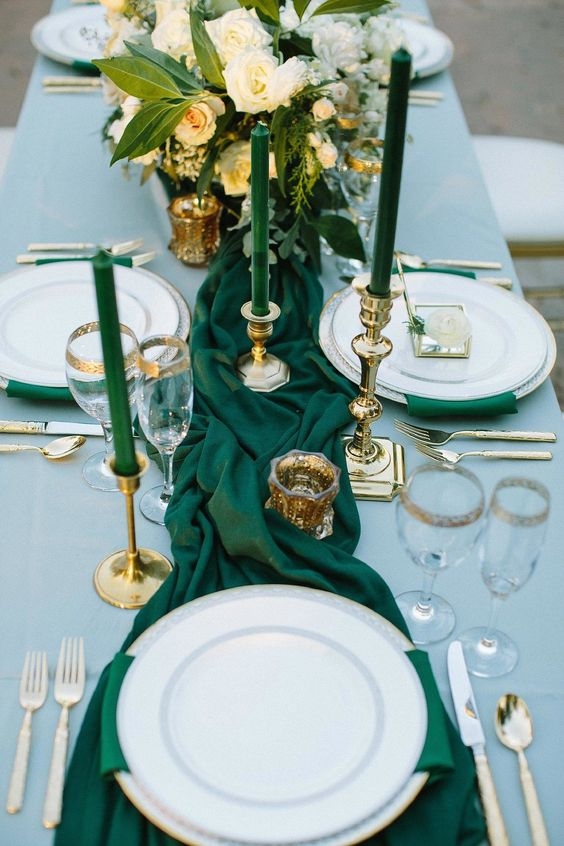 emerald napkins and a table runner, emerald candles in gold candle holders and gold cutlery and gold rim glasses
