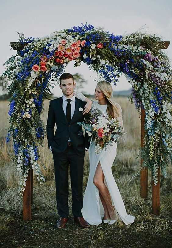 a lush floral arch with peachy roses, white blooms and bold blue flowers on top