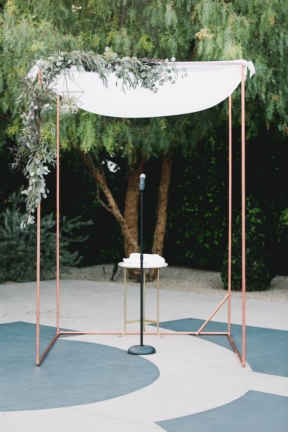 a modern copper arch with airy white fabric, lush greenery and air plants for a chic and cute modern ceremony