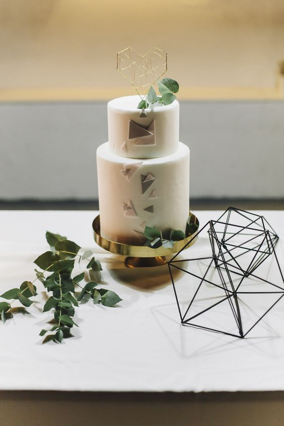 a white wedding cake with colored triangles and topped with a geometric heart and greenery