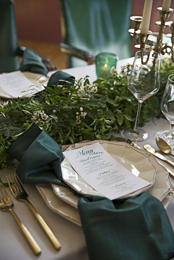 emerald napkins and candleholders, gold cutlery and a lush greenery garland in the center