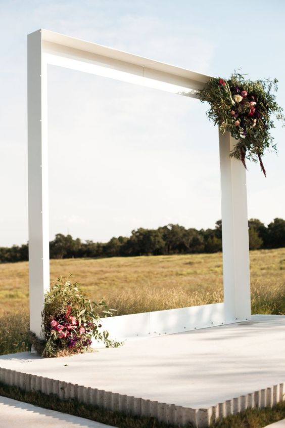 a modern white arch with lush floral and greenery decorations on the corners
