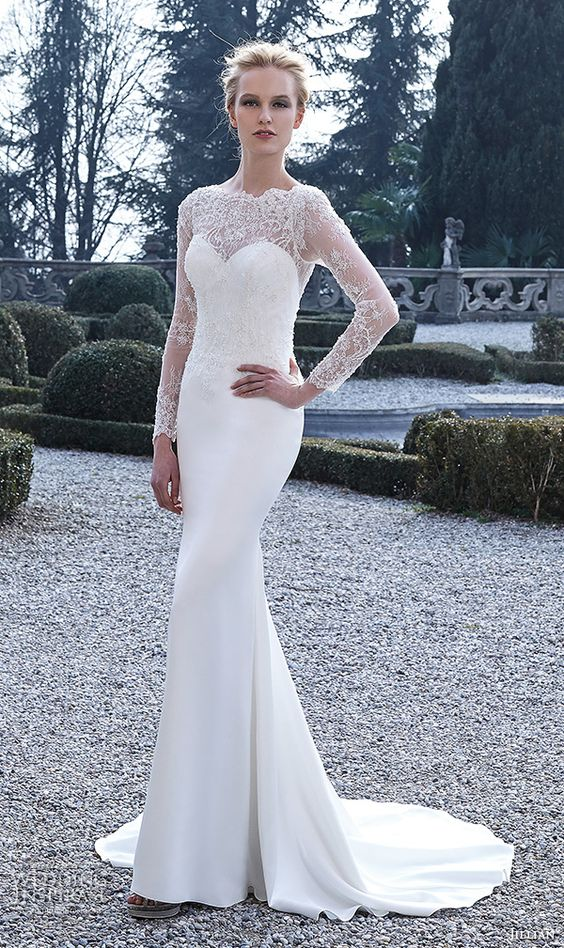 a plain strapless mermaid wedding gown with a sheer lace embellished top with long sleeves over it
