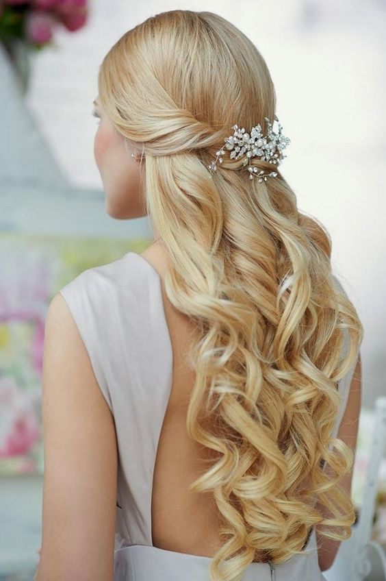 a wavy and twisted half updo on long hair with a gorgeous rhinestone hairpiece