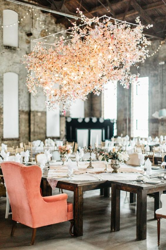 an oversized floral and light chandelier over the reception makes the space cuter