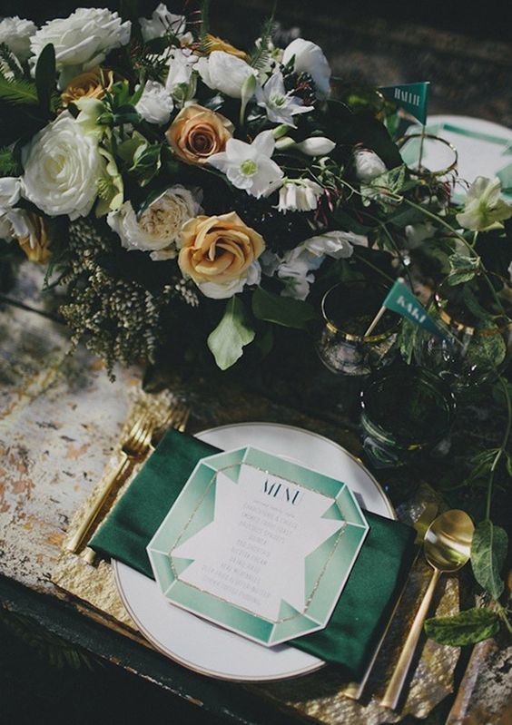 emerald napkins, drink stirrers, gold cutlery and gold rim glasses with a lush floral centerpiece