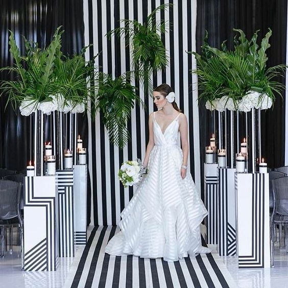 a monochrome striped wedding backdrop with matching pillars and greenery arrangements