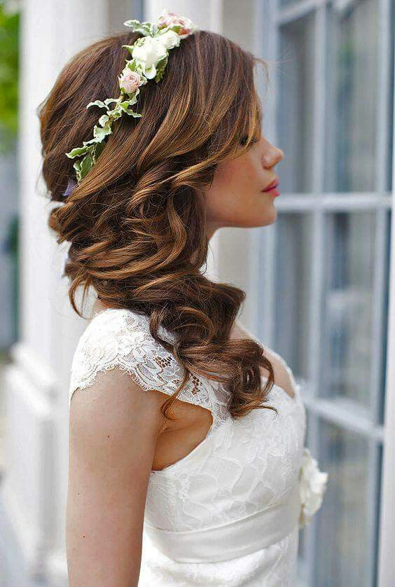 a wavy and twisted side half updo accessorized with a fresh flower crown