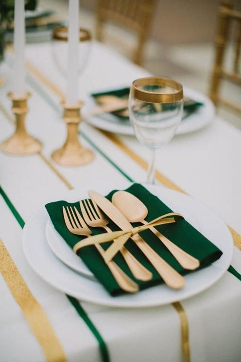 gold cutlery, gold rim glasses and gold candleholders plus emerald napkins