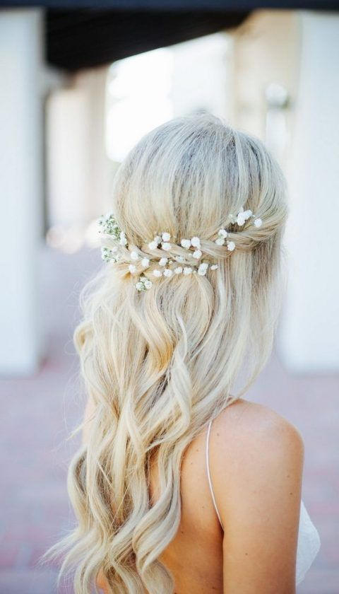 a half updo with a twist and waves and baby's breath tucked in the hair for a boho bride