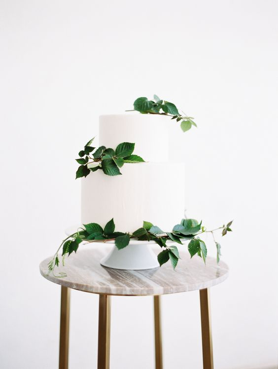 a modern white wedding cake with fresh foliage for a cool and bold look