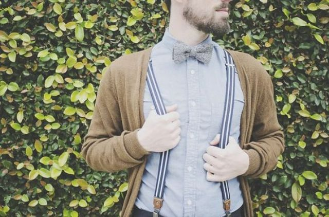 a neutral cardigan over a blue shirt and striped suspenders for a relaxed vintage and rustic look