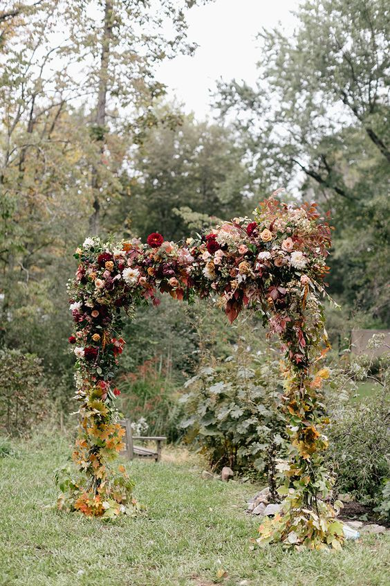 a super lush floral wedding arch in burgundy and pink shades, with lots of fall leaves to embrace the season