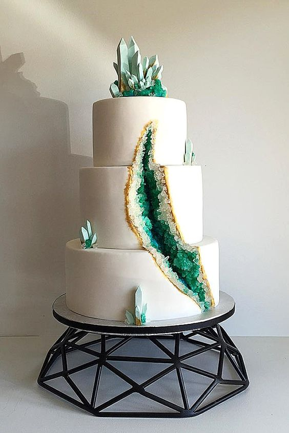 a geode wedding cake with a gold edge and emeralds inside
