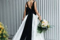 25 a modern A-line wedding dress with black straps and an oversized bow on the back