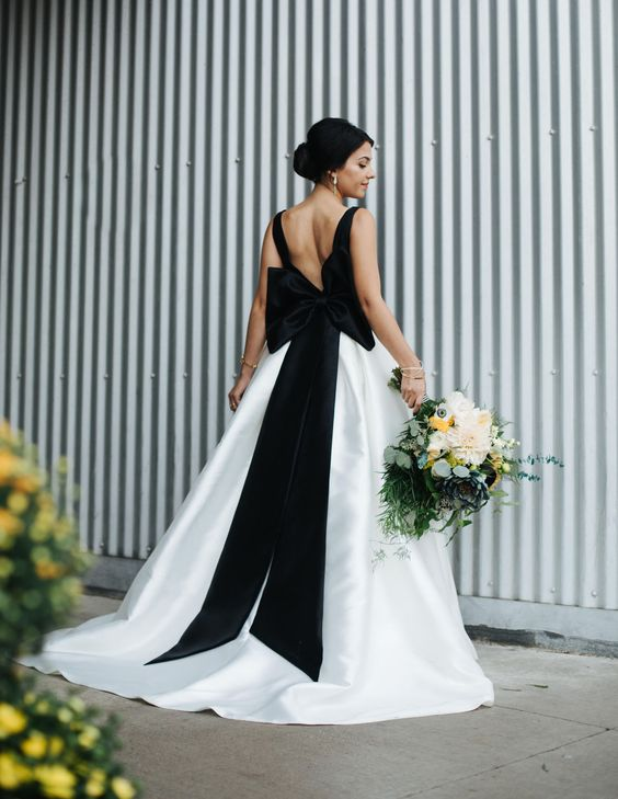 a modern A-line wedding dress with black straps and an oversized bow on the back