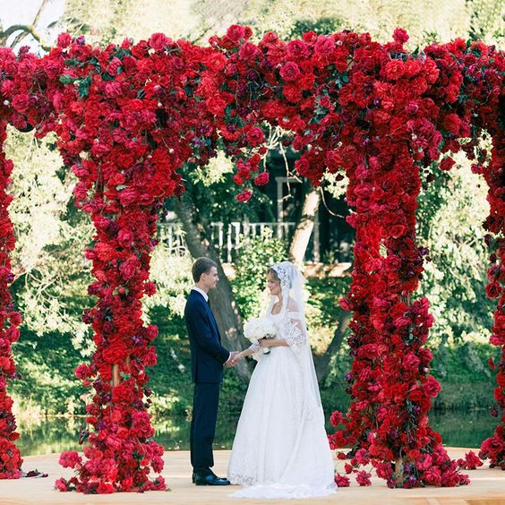 a super lush red floral arch can be seen from a distance and sets the tone to the wedding